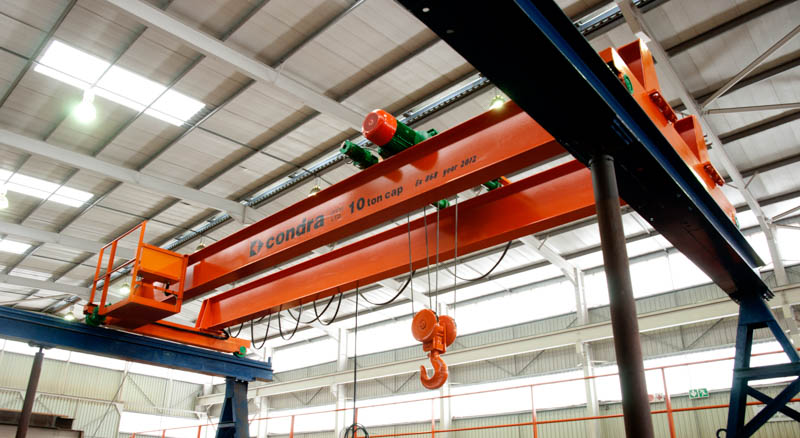 Typical Condra double-girder overhead crane under test. The end-carriages are the 'feet' at each end (with green wheels) to which the twin girders are fixed. Image credit: Condra